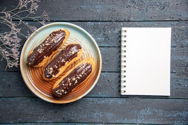 Vista superior de éclairs de chocolate em um galho de flor seca em placa oval e um caderno na mesa de madeira escura