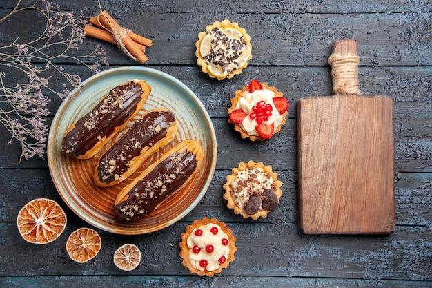Vista superior de éclairs de chocolate em um prato oval cercado por tortas de limão seco e canela e uma tábua de cortar na mesa de madeira escura