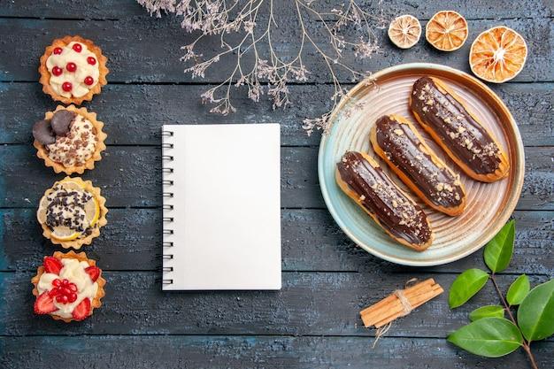 Vista superior de éclairs de chocolate em um prato oval de flores secas, canela, ramos de laranjas secas, folhas de um caderno e tortas verticais no chão de madeira escura