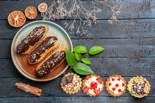 Vista superior de éclairs de chocolate em um prato oval de tortas com laeves de laranjas secas com canela e na mesa de madeira escura com espaço de cópia