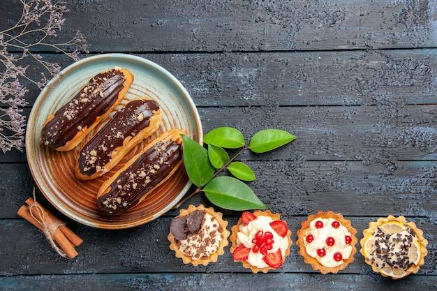 Vista superior de éclairs de chocolate em um prato oval, tortas de canela e salgadinhos na mesa de madeira escura com espaço de cópia