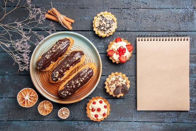 Vista superior de éclairs de chocolate em uma placa oval cercada com tortas de limão seco e canela e um caderno na mesa de madeira escura com espaço de cópia
