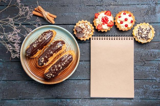 Vista superior de éclairs de chocolate em uma placa oval com galhos de flores secas de canela e um caderno na mesa de madeira escura
