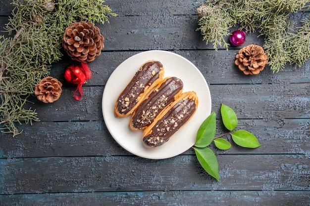 Vista superior de éclairs de chocolate em uma placa oval cones brinquedos de natal folhas de pinheiro em chão de madeira escura com espaço livre