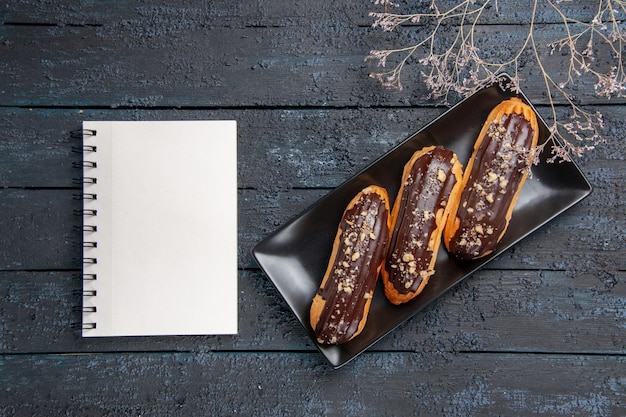 Vista superior de eclairs de chocolate em uma placa retangular e um caderno na mesa de madeira escura com espaço livre