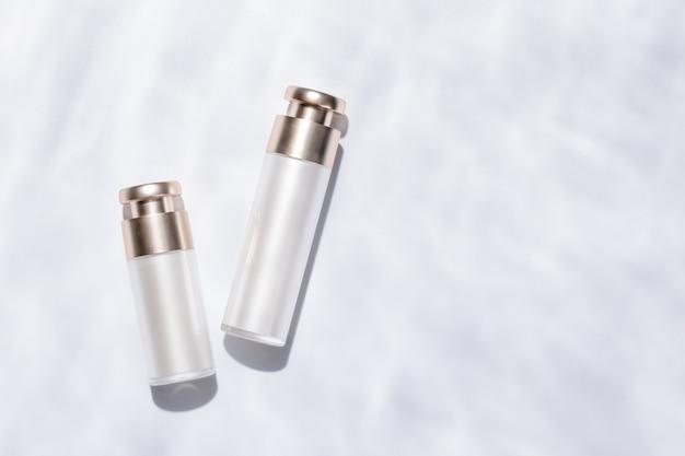 Vista superior de elegantes frascos de cuidados com a pele em uma superfície texturizada branca