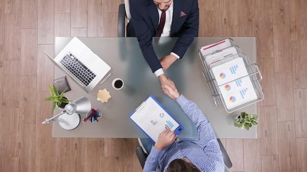Vista superior de empresários apertando as mãos durante a negociação comercial no escritório de inicialização