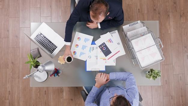 Vista superior de empresários discutindo a estratégia da empresa, analisando a papelada de marketing