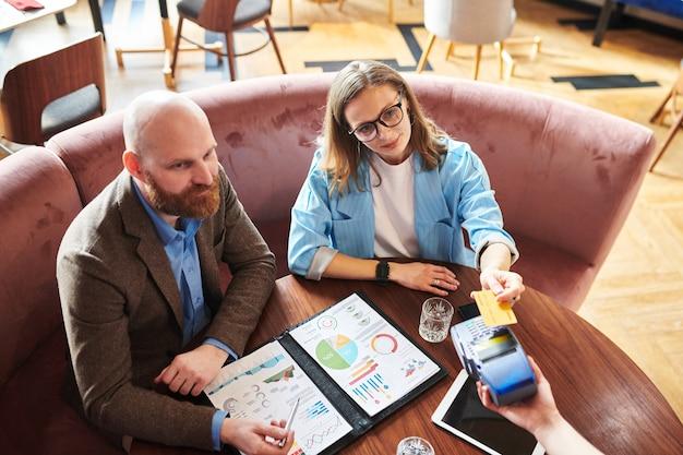 Vista superior de empresários sentados à mesa com relatório financeiro e pagando com smartphone no restaurante