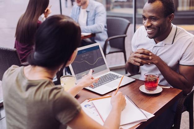 Vista superior de energéticos e ambiciosos dois colegas trabalhando em um café enquanto uma mulher segurando um lápis e apontando para a tela
