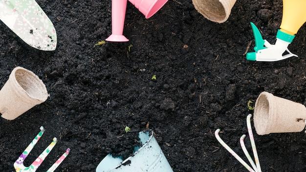 Vista superior de equipamentos de jardinagem dispostos em solo preto