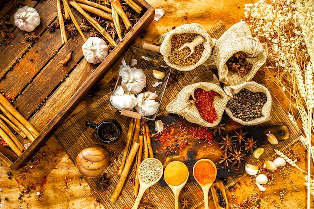 Vista superior de ervas, pimenta, pimenta em colheres, alho, especiarias em sacos, canela,