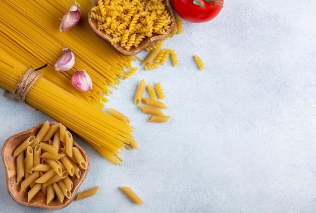 Vista superior de espaguete cru com macarrão cru em tigelas com alho e tomate em uma superfície cinza