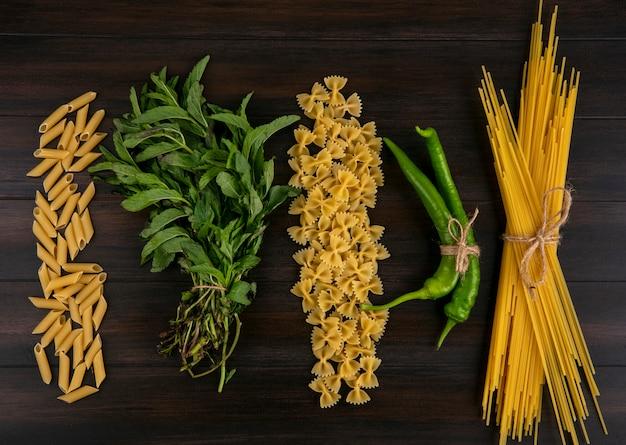 Vista superior de espaguete cru com macarrão de pimenta e um punhado de hortelã em uma superfície de madeira