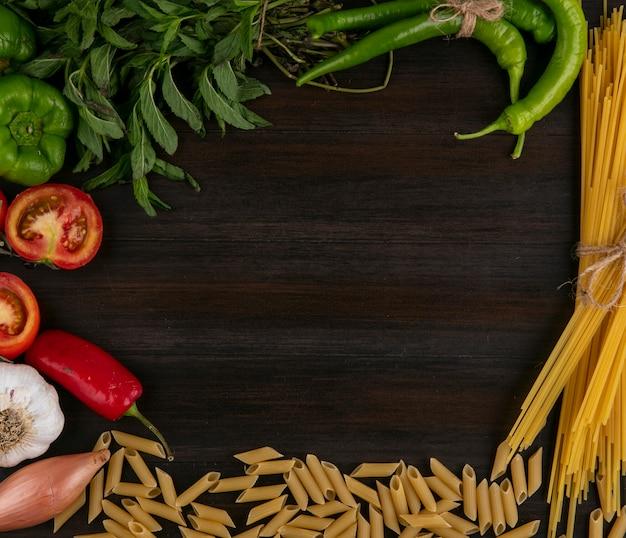 Vista superior de espaguete cru com macarrão, tomate, pimentão e alho com hortelã em uma superfície de madeira
