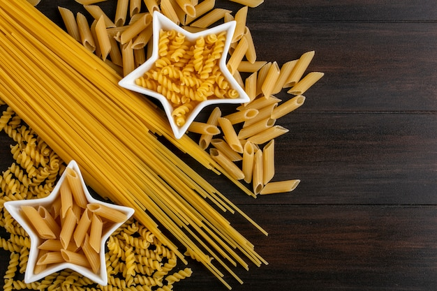 Vista superior de espaguete cru com massa crua em pires em forma de estrela na superfície de madeira