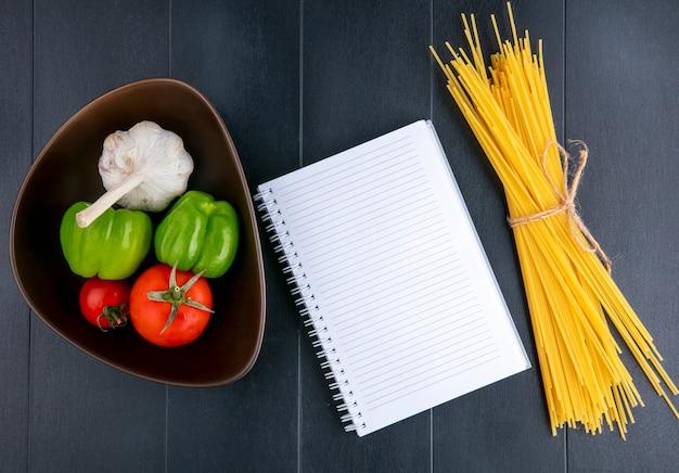 Vista superior de espaguete cru com tomate, alho e pimentão em uma tigela e um bloco de notas em uma superfície preta