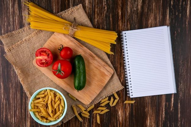 Vista superior de espaguete cru com tomate e pepino em uma tábua com um caderno em um guardanapo bege em uma superfície de madeira