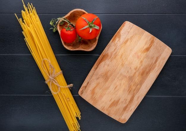 Vista superior de espaguete cru com tomate e quadro-negro em uma superfície preta