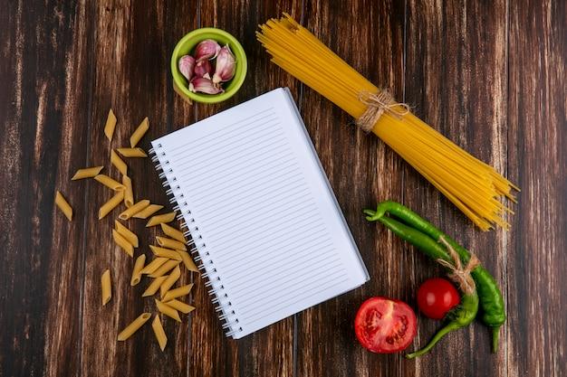 Vista superior de espaguete cru com tomate pimenta e caderno na superfície de madeira