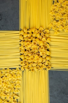Vista superior de espaguete cru e conchiglie seco e farfalle no preto