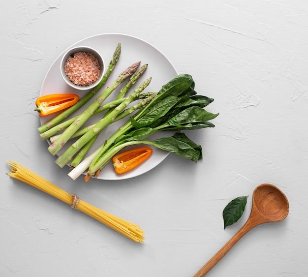 Vista superior de espargos no prato com sal do himalaia e espaguete cru