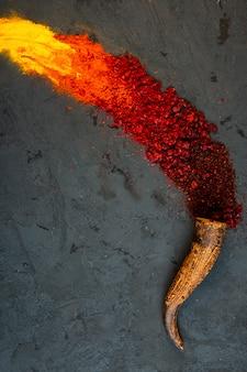 Vista superior de especiarias de pimenta vermelha e sumagre em pó com curry espalhados de um chifre no preto