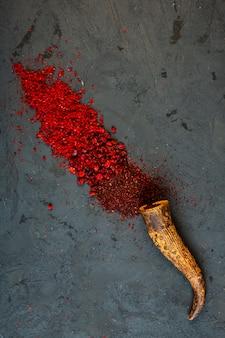 Vista superior de especiarias de pimenta vermelha e sumagre em pó espalhadas de um chifre no preto