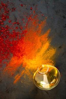 Vista superior de especiarias em pó de pimenta vermelha e sumagre com curry e páprica e uma garrafa de azeite