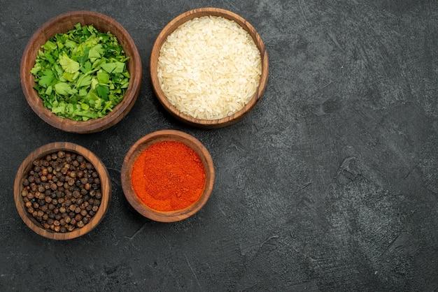Vista superior de especiarias em tigelas ervas de papel preto, especiarias coloridas e arroz no lado esquerdo da mesa escura