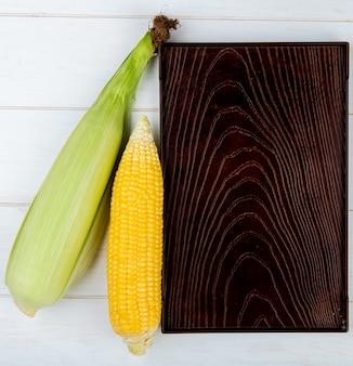 Vista superior de espigas de milho com bandeja na madeira