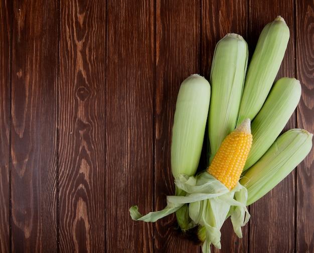 Vista superior de espigas de milho com casca na madeira com espaço de cópia