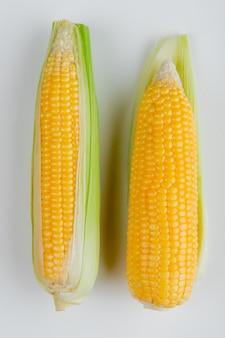 Vista superior de espigas de milho com casca na superfície branca
