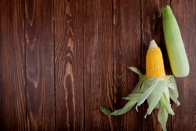 Vista superior de espigas de milho com casca na superfície de madeira com espaço de cópia