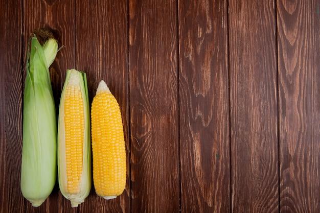 Vista superior de espigas de milho com casca no lado esquerdo e madeira com espaço de cópia