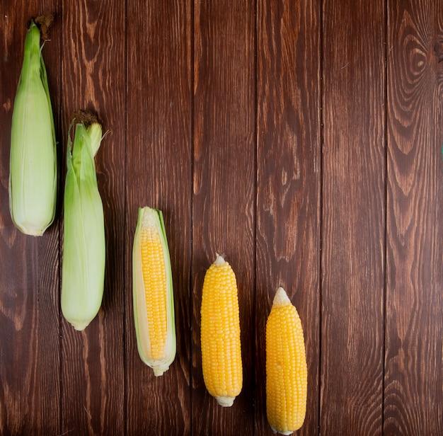 Vista superior de espigas de milho cozidas e não cozidas no lado esquerdo e madeira com espaço de cópia