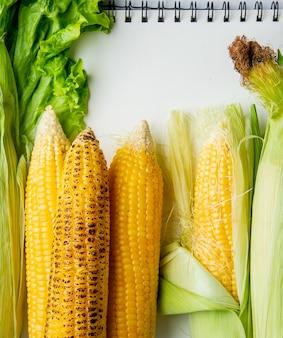 Vista superior de espigas de milho e alface com bloco de notas como superfície
