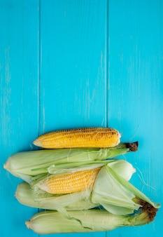 Vista superior de espigas de milho na superfície azul com espaço de cópia