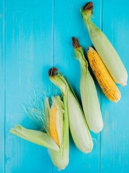 Vista superior de espigas de milho na superfície azul