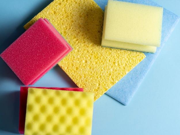 Vista superior de esponjas de limpeza de diferentes cores e tamanhos dispostas em um fundo azul