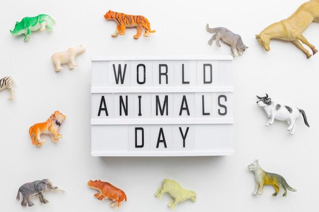 Vista superior de estatuetas de animais com caixa de luz para o dia animal