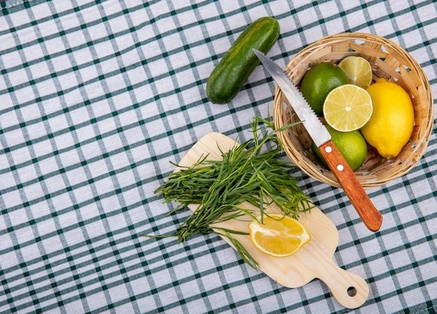 Vista superior de estragão verdes em uma placa de cozinha de madeira com rodelas de limão com um balde de limões frescos com faca na superfície da toalha de mesa marcada