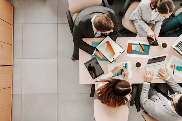 Vista superior de executivos caucasianos com roupa formal, sentados na sala de reuniões na mesa e analisando dados. na mesa estão laptops, gráficos, tablets e papelada.