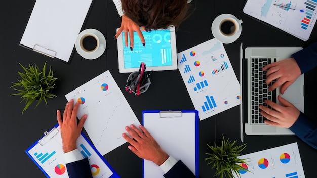 Vista superior de executivos reunidos para analisar gráficos de estatísticas financeiras, planejando o próximo projeto usando dispositivos digitais no escritório corporativo
