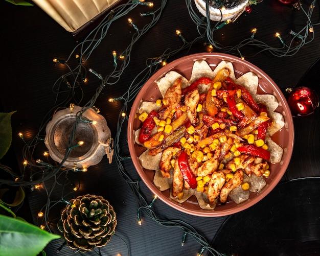 Vista superior de fajitas de frango com molho de tomate e milho vermelho pimentão amarelo