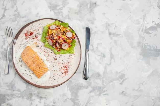 Vista superior de farinha de peixe e salada deliciosa em um prato e talheres colocados no lado esquerdo em uma superfície branca manchada