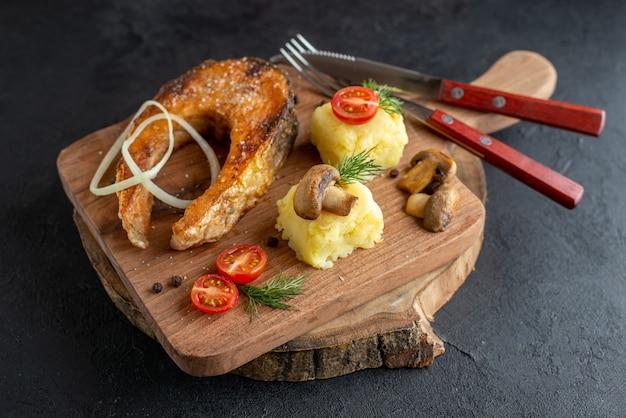 Vista superior de farinha de peixe frito com cogumelos, vegetais, queijo e talheres em uma placa de madeira na superfície preta afligida