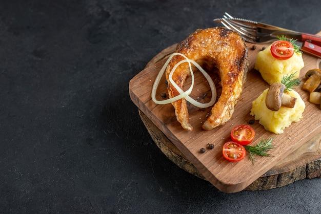Vista superior de farinha de peixe frito com cogumelos, vegetais, queijo e talheres em uma placa de madeira no lado esquerdo em uma superfície preta desgastada
