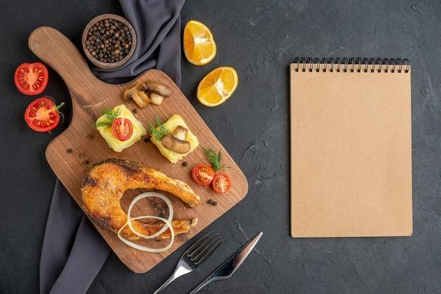 Vista superior de farinha de peixe frito com cogumelos, vegetais, queijo, tábua de madeira, fatias de limão, pimenta na toalha de cor escura, conjunto de talheres e caderno na superfície preta angustiada