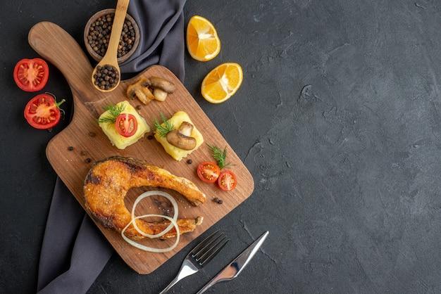 Vista superior de farinha de peixe frito com queijo de vegetais de cogumelos na placa de madeira rodelas de limão pimenta na toalha de cor escura no lado direito na superfície preta angustiada